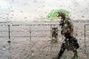 An dem regennassen Windschutz eines Straßencafes und vor dem Hintergrund des Hamburger Hafens geht am Morgen des 4.7.2003 eine Frau mit Schirm auf dem Weg zur Arbeit vorbei.